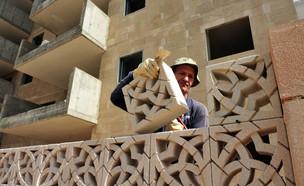 פועל מניח לבנים באתר בנייה באשדוד (אילוסטרציה: kateafter | Shutterstock.com )