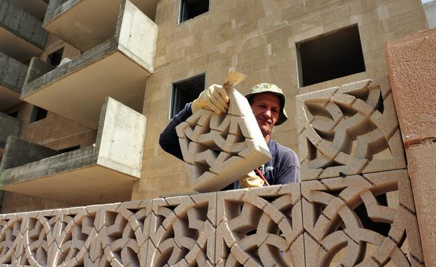 פועל מניח לבנים באתר בנייה באשדוד (אילוסטרציה: By Dafna A.meron, shutterstock)