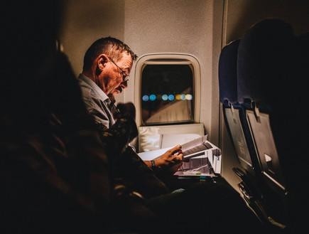 איש יושב ליד החלון במטוס (צילום: unsplash)