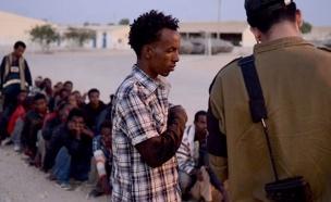 """חיילי הליווי עם המסתננים בגבול (צילום: בן אברהם, """"במחנה"""")"""