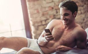 גבר במיטה עם טלפון (צילום: 4 PM production, Shutterstock)