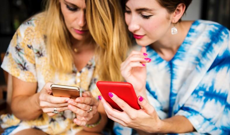 שתי נשים מביטות בטלפונים סלולריים (צילום: rawpixel.com, unsplash)
