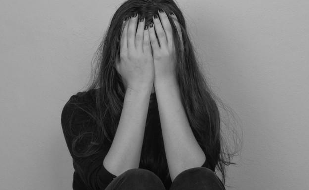 אישה מכסה את פניה (צילום: shutterstock)