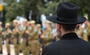 אדם חרדי עומד ליד חיילים (צילום: By Dafna A.meron, shutterstock)