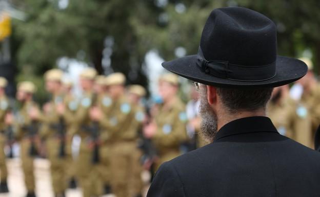 אדם חרדי עומד ליד חיילים