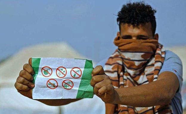 """פלסטיני מחזיק בכרוז אזהרה של צה""""ל (צילום: כלי תקשורת פלסטינים)"""