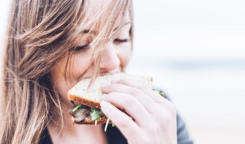 אישה אוכלת כריך (צילום: gardie design social media marketing-unsplash)