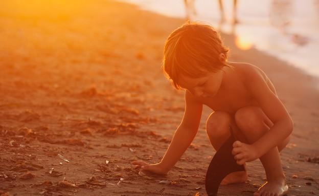 ילד משחק על החוף עם הוריו ברקע (צילום: monica gozalo, unsplash)