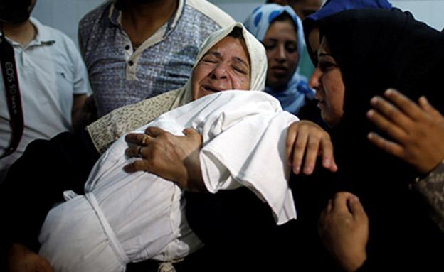 התינוקת בזרועות בני משפחתה (צילום: רויטרס)