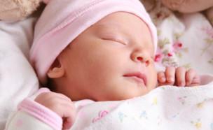 תינוקת ישנה על הגב מחייכת (צילום: אימג'בנק / Thinkstock)