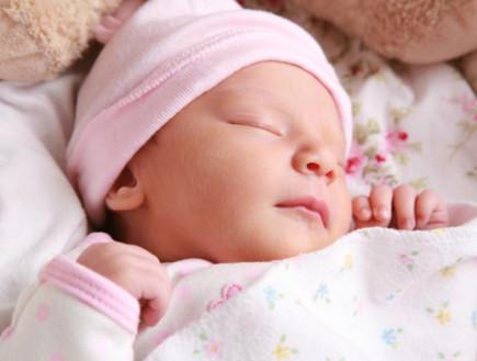 תינוקת ישנה על הגב מחייכת