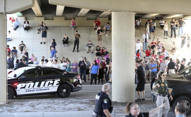 תלמידים ושוטרים בזירת הירי בפלורידה (צילום: AP)