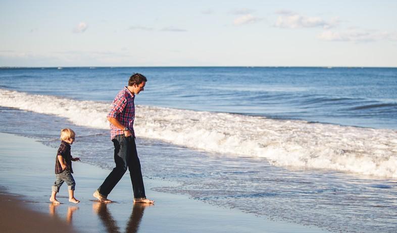 אבא ובן מטיילים על חוף הים (אילוסטרציה: Danielle MacInnes, unsplash)