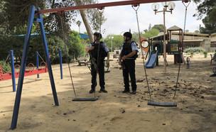 שוטרים שומרים על גן משחקים בקיבוץ בעוטף עזה (צילום: Tsafrir Abayov, ap)