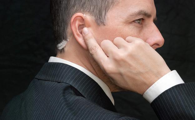 סוכן חשאי שם אצבע על אוזניה באוזן - אילוסטרציה (צילום: David Stuart Productions, ShutterStock)