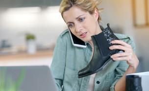 אישה מדברת בטלפון מול מחשב (אילוסטרציה: goodluz, shutterstock)