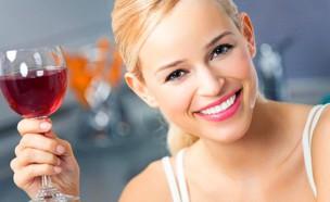 אישה מחייכת מחזיקה כוס יין (צילום: אימג'בנק/Thinkstock)