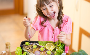ילדה אוכלת דג (אילוסטרציה: By Dafna A.meron, shutterstock)
