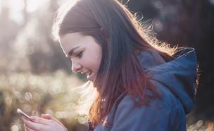 אישה מסתכלת על טלפון סלולרי (אילוסטרציה: luke porter, unsplash)