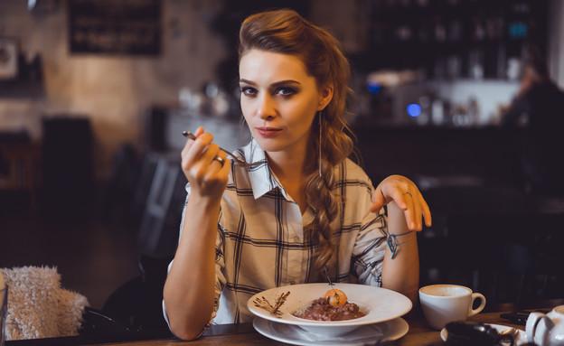 בחורה אוכלת במסעדה (צילום:  sergey causelove, shutterstock)