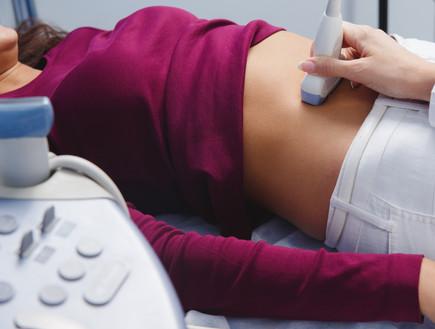 אישה בשלבים ראשונים של היריון עוברת בדיקת אולטרהסאונד