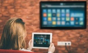 אישה שולטת על טלוויזיה חכמה מטאבלט (צילום: Rasulov, shutterstock)