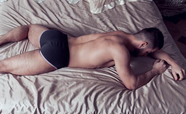 גבר שוכב על הבטן (צילום: Alex Gudov, ShutterStock)