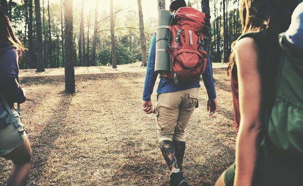 גבר ושתי נשים מטיילים עם תרמילים ביער (צילום: Rawpixel.com, ShutterStock)