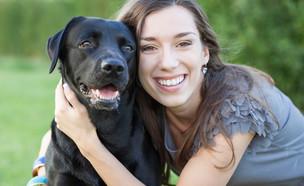 אישה עם כלב שחור (צילום:  MorePixelsShutterstock)