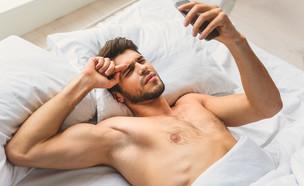גבר במיטה עם הטלפון (צילום: Olena Yakobchuk, Shutterstock)