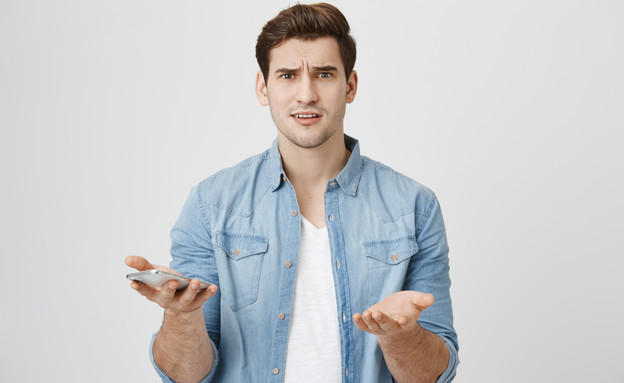 גבר עם סמארטפון (צילום: Cookie Studio, Shutterstock)