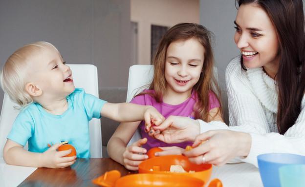 אמא צעירה מאכילה שני ילדים