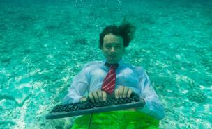 גבר בבגדי עסקים מקליד מתחת למים (צילום: Sergey Novikov, shutterstock)