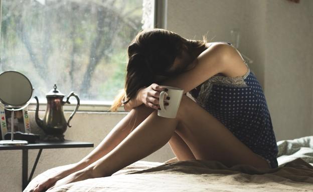 אישה יושבת על מיטה (אילוסטרציה: Asdrubal luna, unsplash)