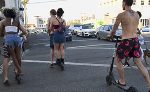 צעירים רוכבים על קורקינטים חשמליים בסנטה מוניקה (צילום: ap)