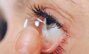אישה מרכיבה עדשות מגע (צילום: Dmytro Khlystun, Shutterstock)