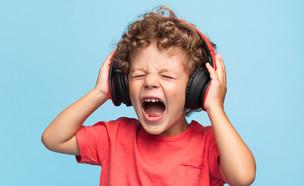 ילד מעוצבן עם אוזניות (צילום: Mark Nazh, shutterstock)