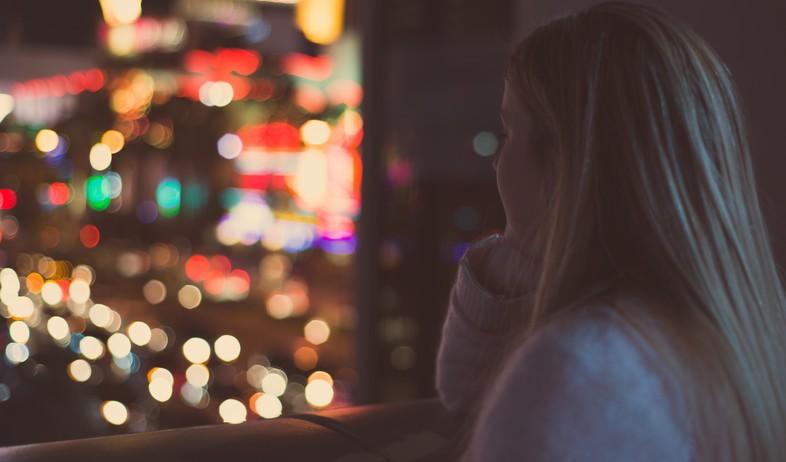אישה מסתכלת מהחלון בלילה (צילום: ryan-pouncy-unsplash)