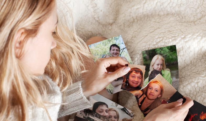 אישה עצובה קורעת צילומים משפחתיים (אילוסטרציה: By Dafna A.meron, shutterstock)