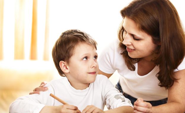 ילד כותב מביט לעבר אמו (צילום: אימג'בנק / Thinkstock)