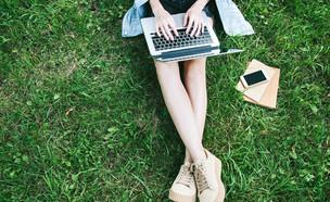 רגליים של אישה משתמשת בלפטופ (צילום:  Kate Aedon, shutterstock)