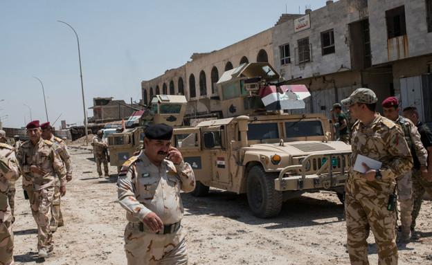 חיילים וקצינים עיראקים בפאתי מוסול (צילום: Martyn Aim, stringer)