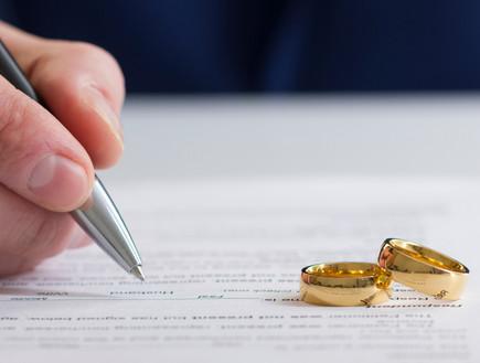 חותם על מסמך עם שתי טבעות על השולחן (צילום:  Roman Motizov, ShutterStock)