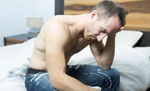 גבר יושב על המיטה (צילום: Lopolo, Shutterstock)