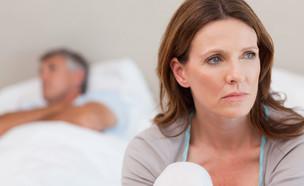 אישה עצובה במיטה וגבר ברקע (צילום: אימג'בנק / Thinkstock)