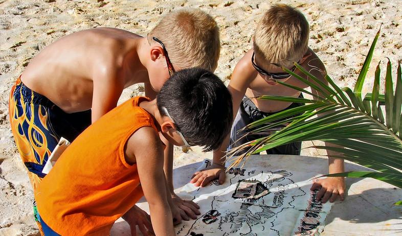 ילדים משחקים עם מפת אוצר - חפש את המטמון (צילום: By Dafna A.meron, shutterstock)