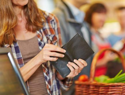 אישה מסתכלת על ארנק ריק בסופרמרקט