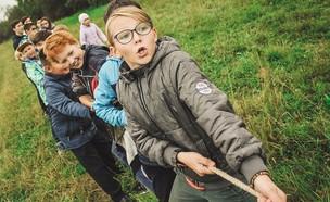 קבוצת ילדים משחקת משיכת חבל (צילום: anna samoylova - unsplash)