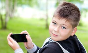 אילוסטרציה: ילד מחזיק סמארטפון (צילום:  BestPhotoPlus, ShutterStock)
