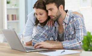 זוג מודאג מסתכל במחשב (צילום: goodluz, shutterstock)